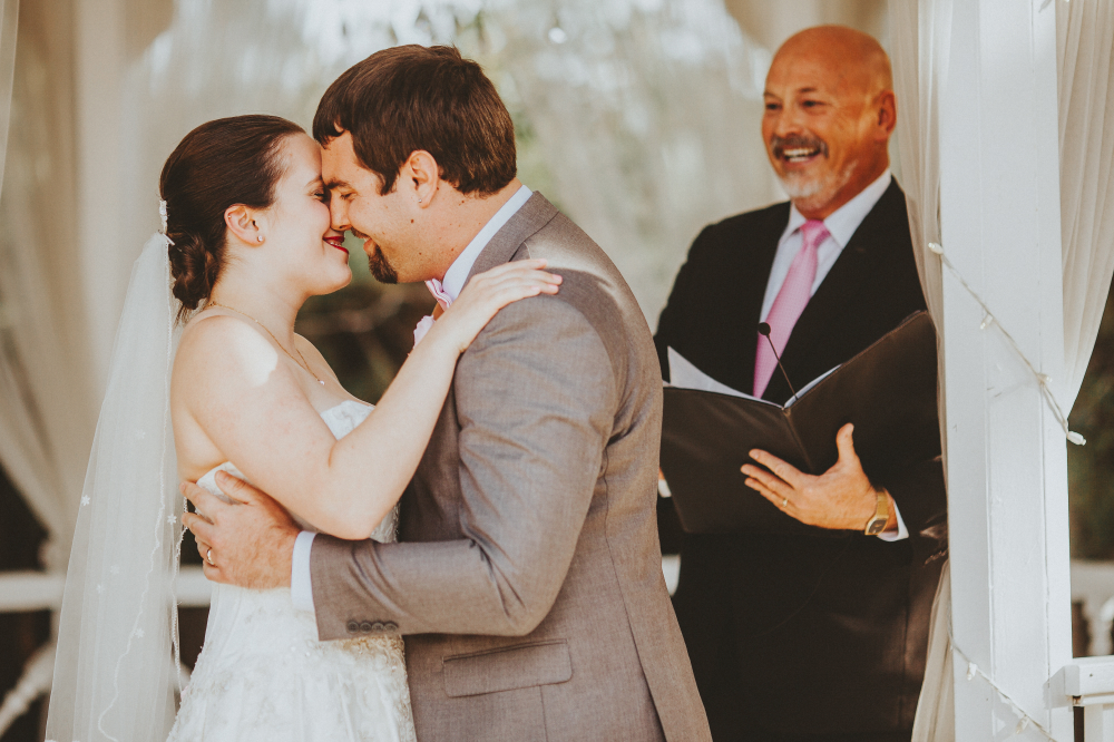 san diego wedding   photographer | groom in grey suit about to kiss bride with officiator   laughing