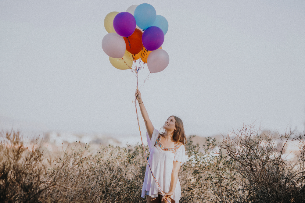 san diego wedding   photographer | woman in white lifting up balloons