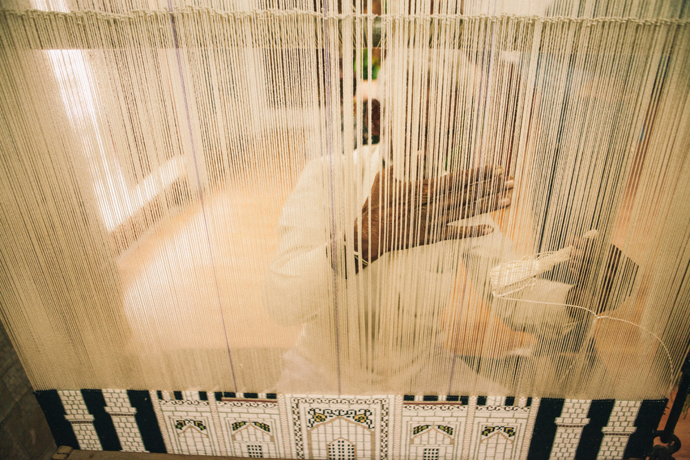 san diego wedding   photographer | man using loom seen from behind strands