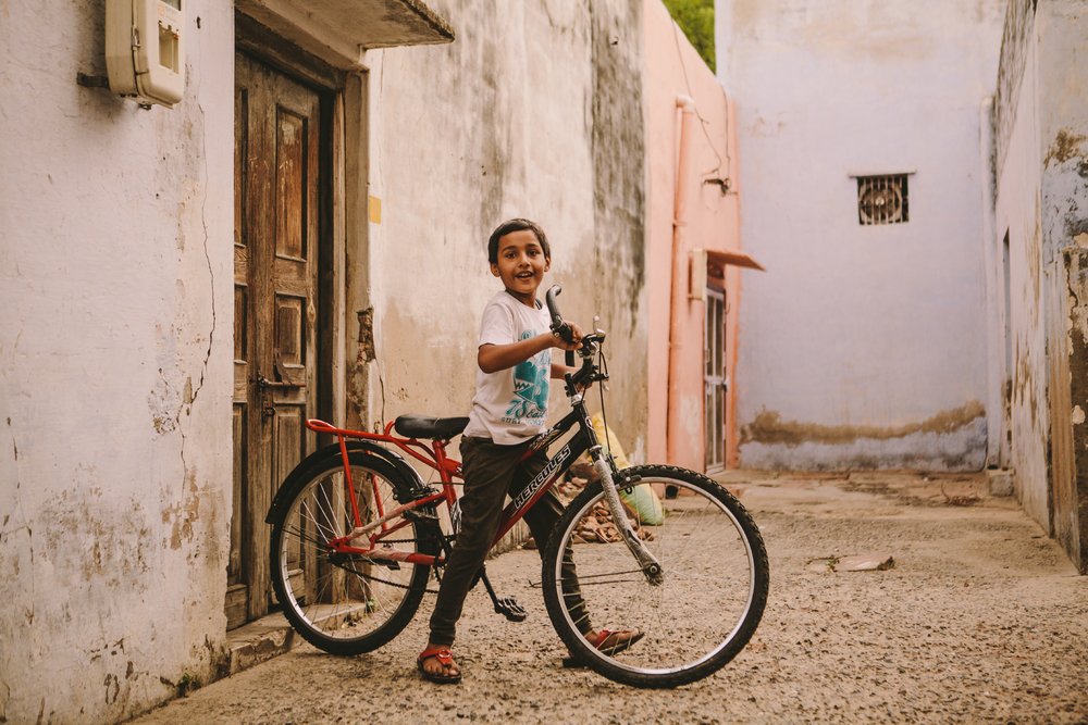 san diego wedding   photographer | kid on bike in alleyway looking at camera