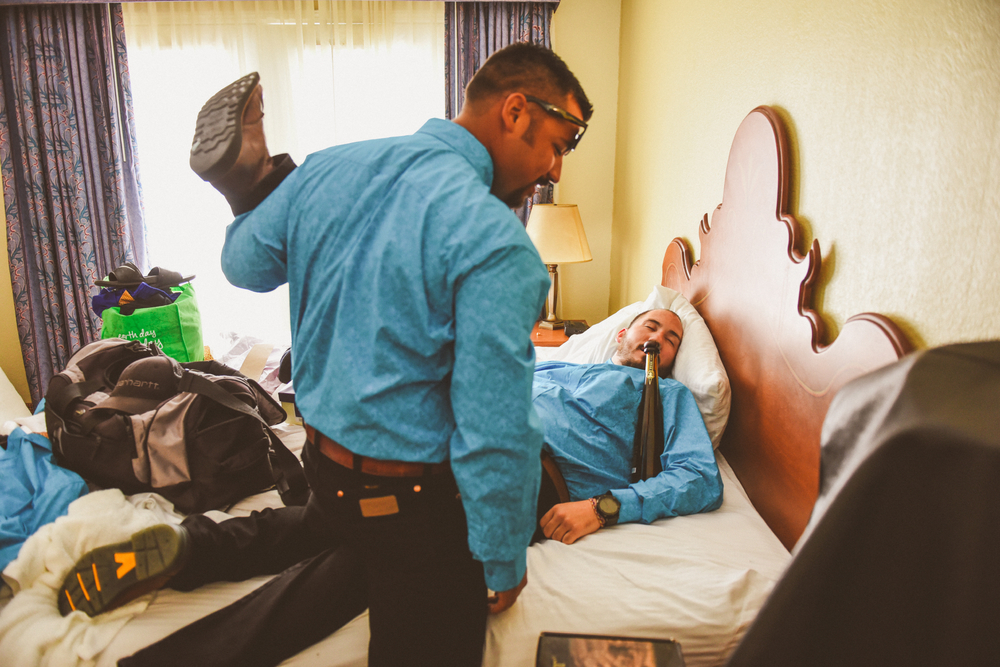 san diego wedding   photographer | man lying on bed with bottle of champagne