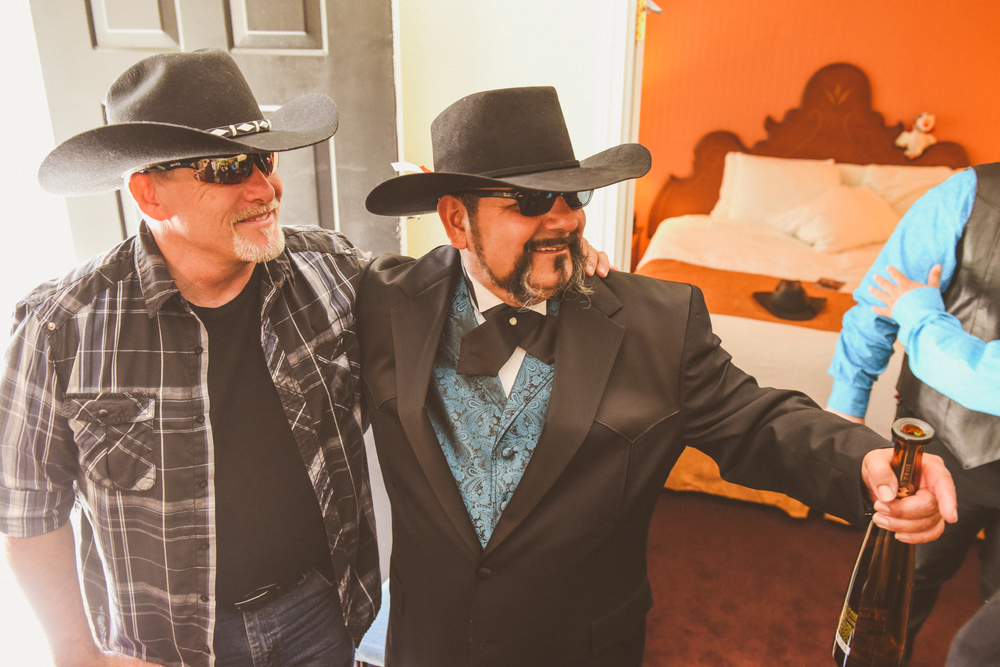 san diego wedding   photographer | men in cowboy hats holding bottle of liquor