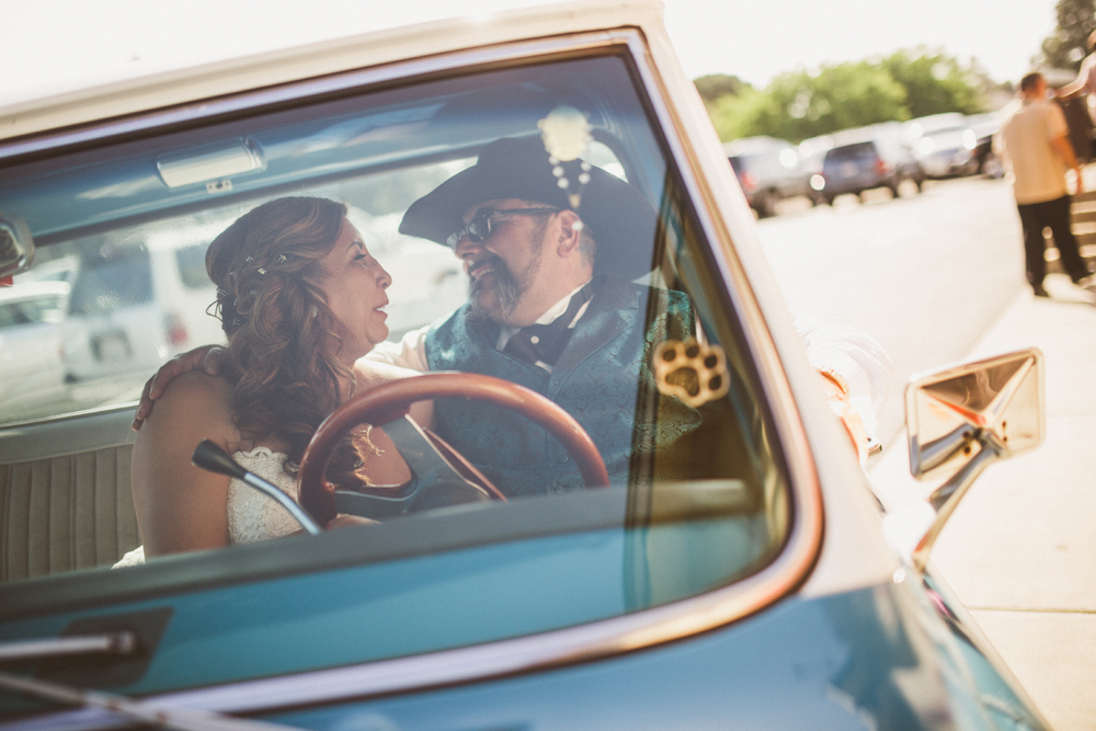 san diego wedding   photographer | groom with cowboy hat and bride facing each other and laughing   inside blue pickup truck with man in background