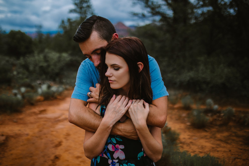 san diego wedding   photographer | man hugging woman in black floral dress from behind