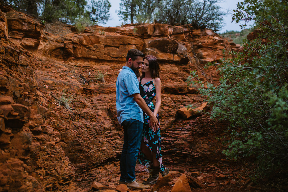 san diego wedding   photographer | bearded man in blue standing on rocks with woman in floral   dress
