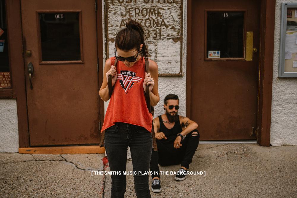 san diego wedding   photographer | woman in van halen shirt walking in front of sitting bearded   man