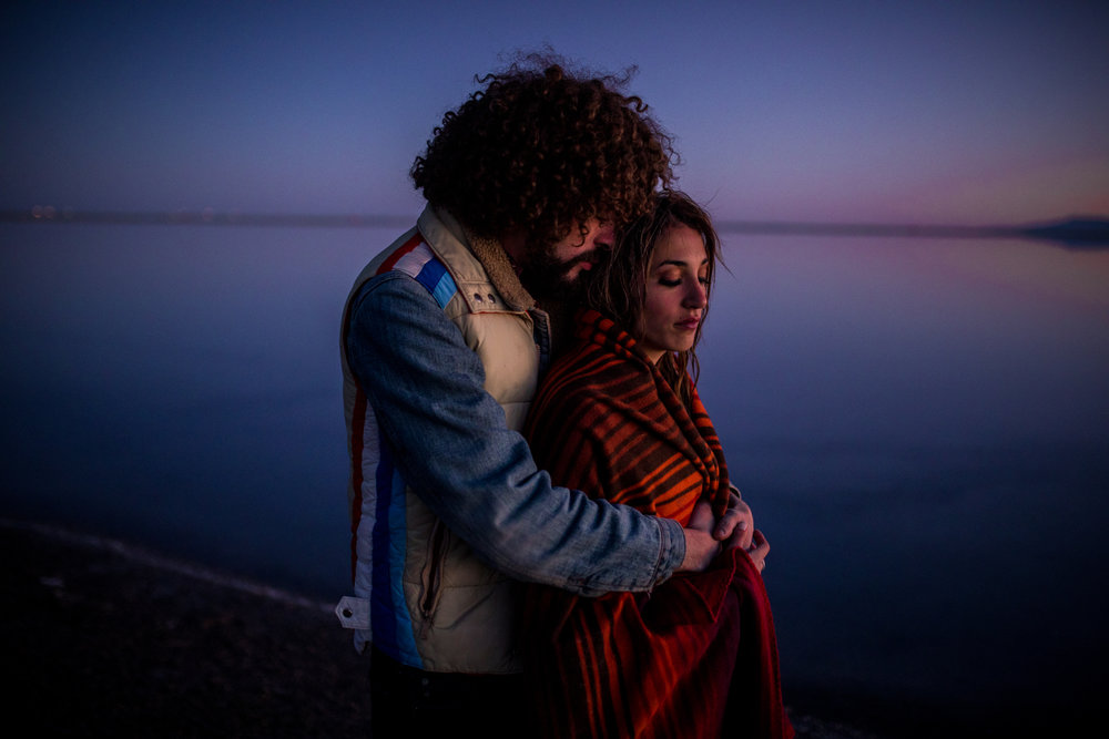 san diego wedding   photographer | man with curly hair and beige vest embracing woman in striped   orange blanket