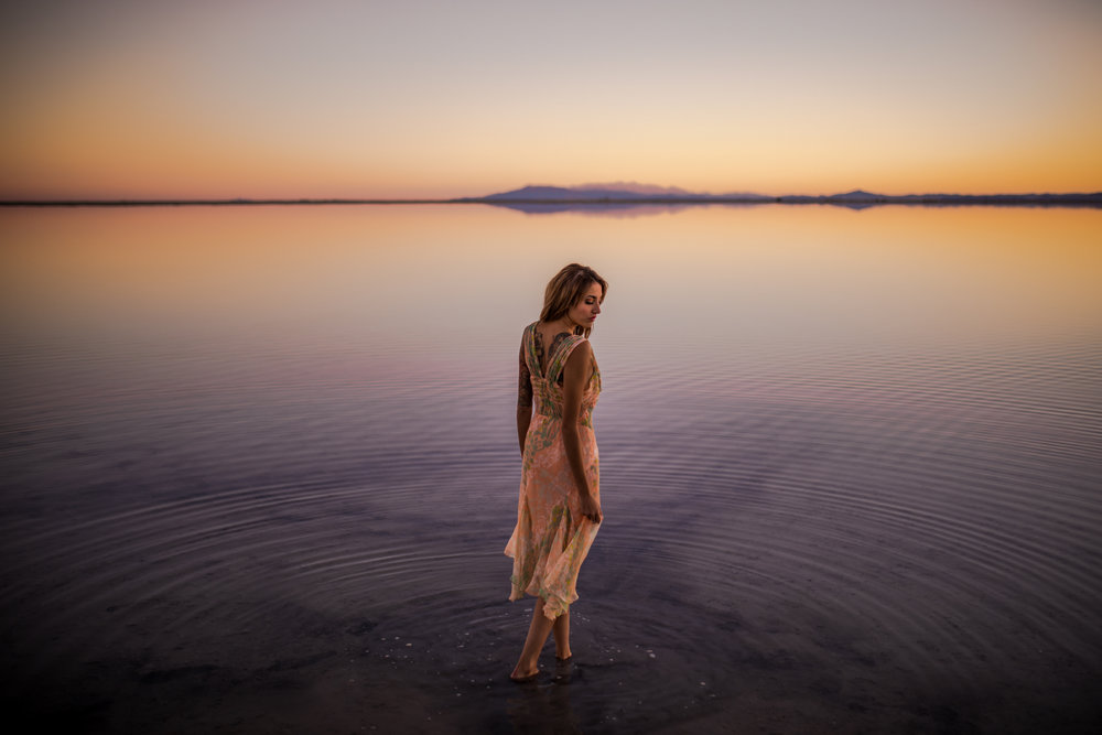 san diego wedding   photographer | whole body shot of woman in floral dress standing on salt   flats and looking at the water