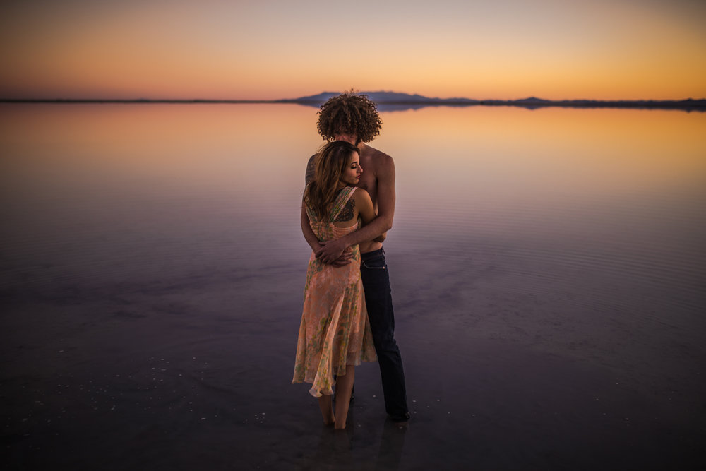 san diego wedding   photographer | tattooed topless man and woman in floral dress facing each   other and hugging while standing on salt flats