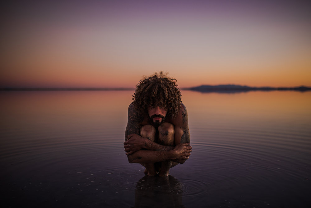 san diego wedding   photographer | close-up of tattooed naked man sitting and embracing self on   salt flats