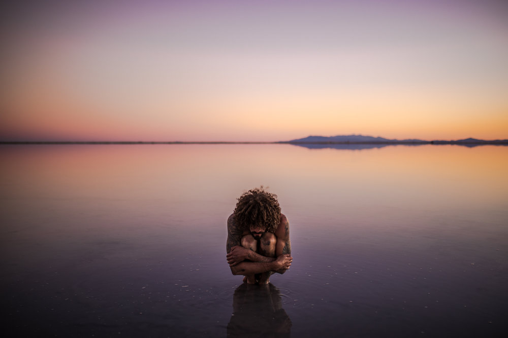 san diego wedding   photographer | tattooed naked man sitting and embracing self on salt flats