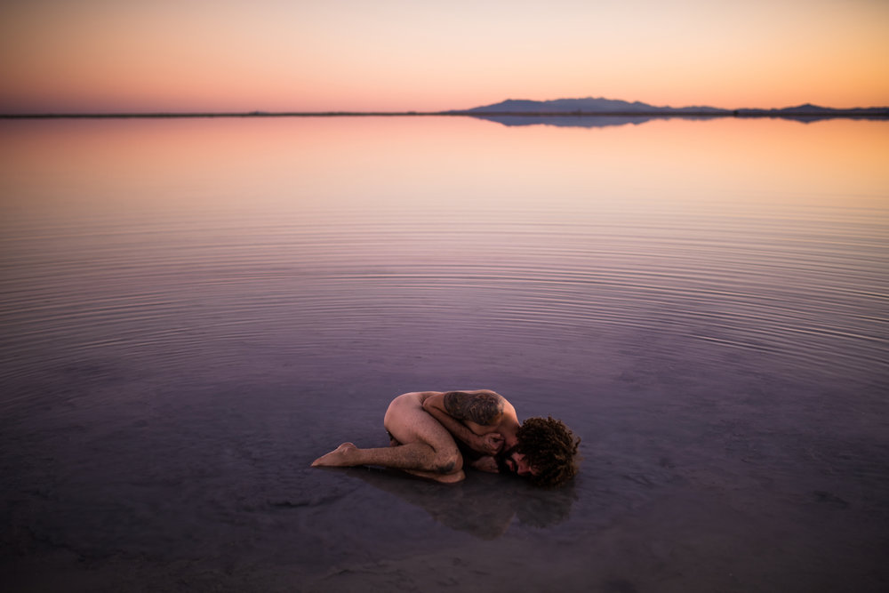 san diego wedding   photographer | tattooed naked man lying in fetal position on salt flats