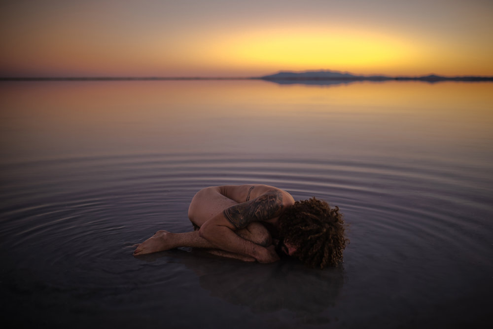 san diego wedding   photographer | close-up of tattooed naked man lying in fetal position on salt   flats