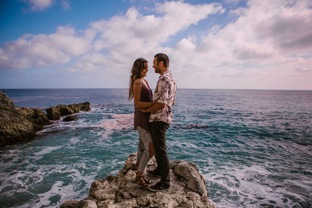 san   diego wedding photographer | woman in ripped jeans smiling at man on rock