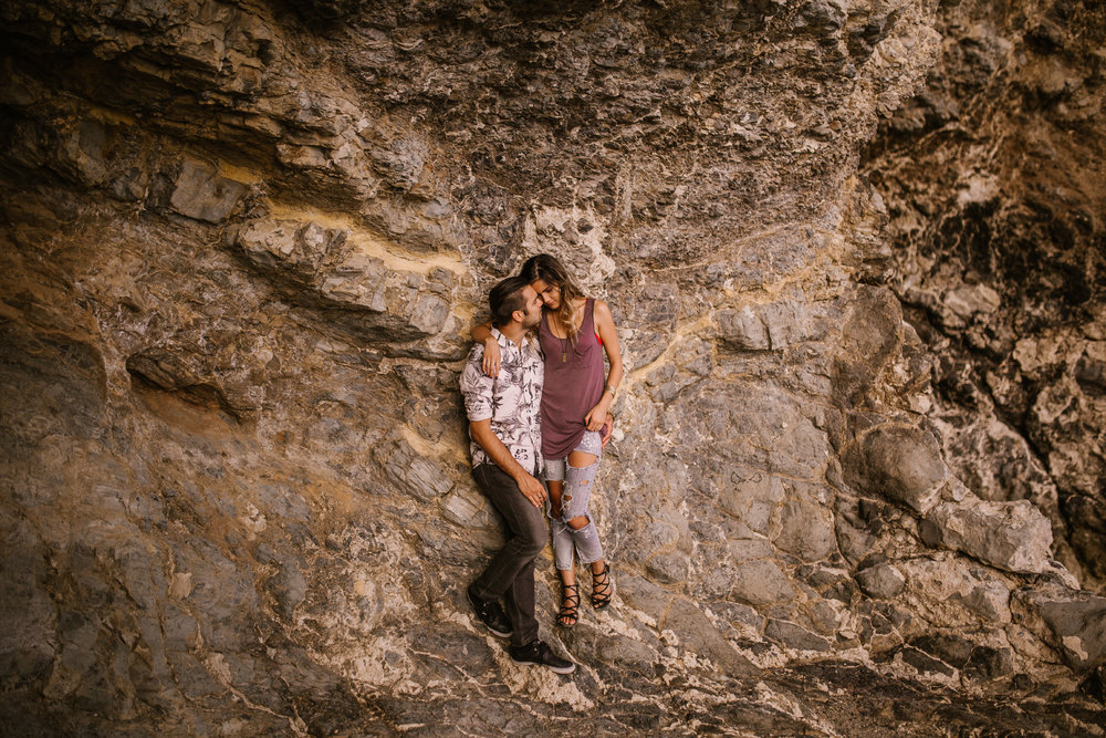 san   diego wedding photographer | man holding woman around waist leaning against   rock wall