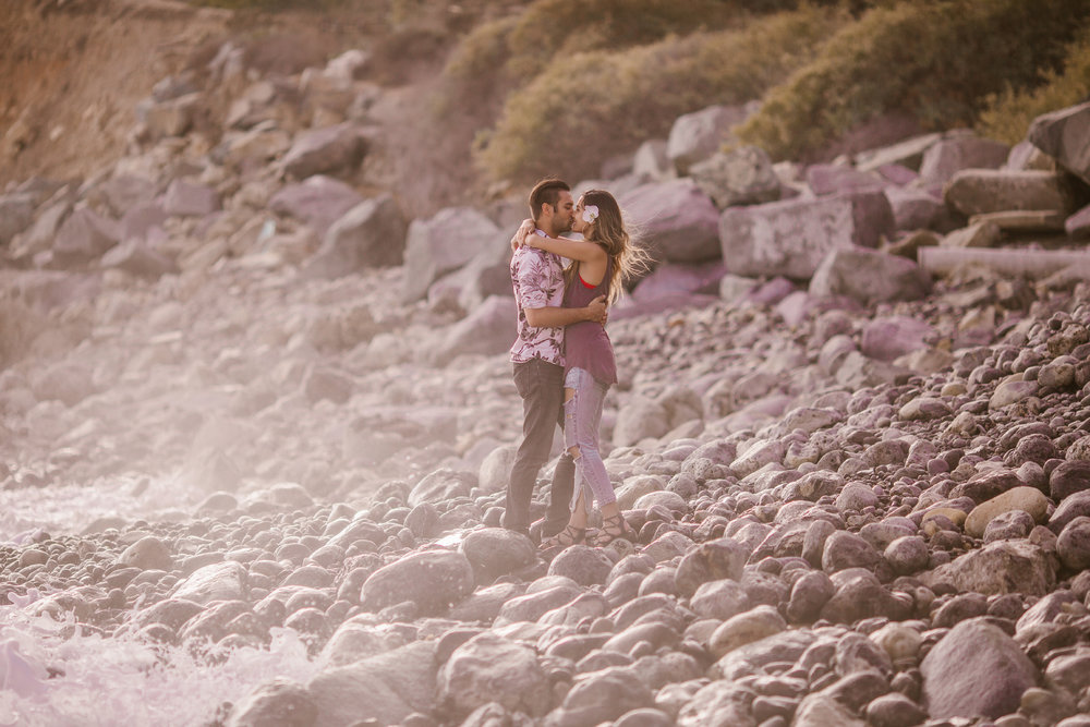san diego wedding photographer | far shot of man and woman kissing each other while wave crashes on rocky shore