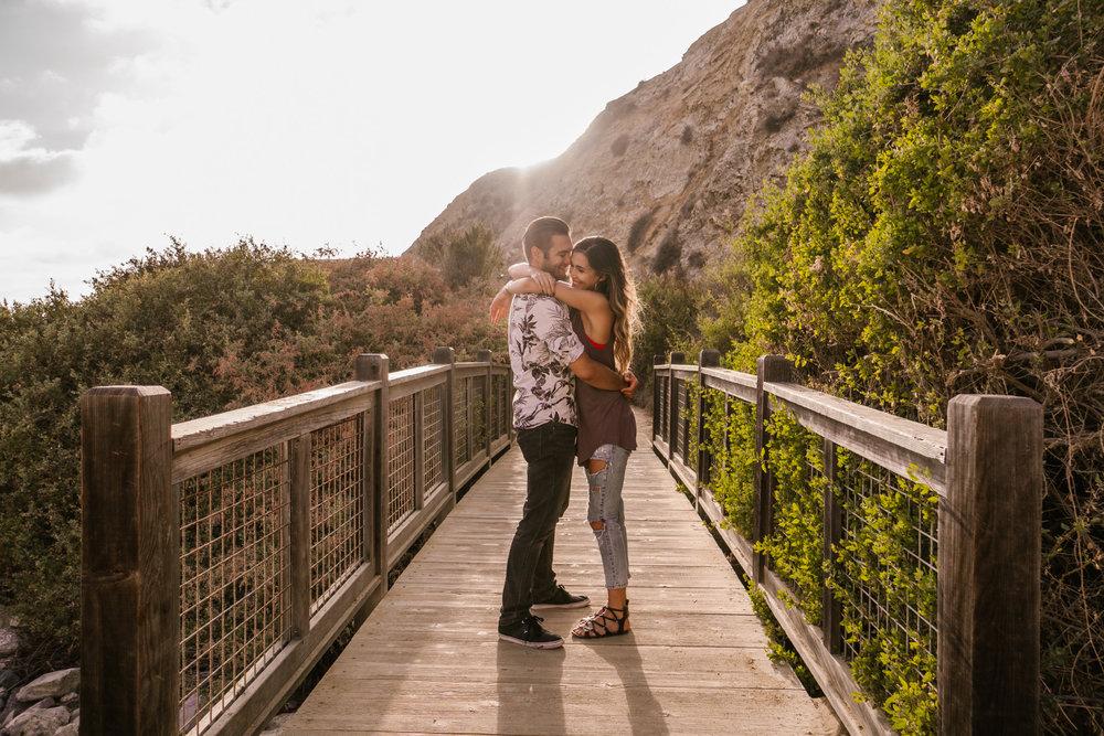 san diego wedding photographer   woman about to hug man on bridge illuminated by sun