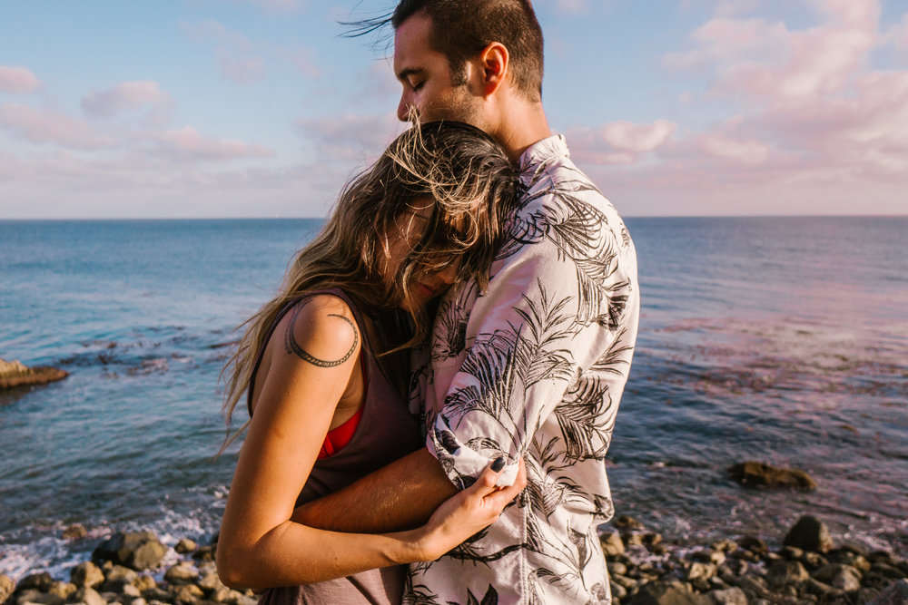 san diego wedding photographer | man hugging woman with arms around each other on rocky shore