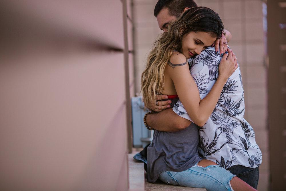 san   diego wedding photographer   woman in faded purple tank top sitting on window   ledge hugging man
