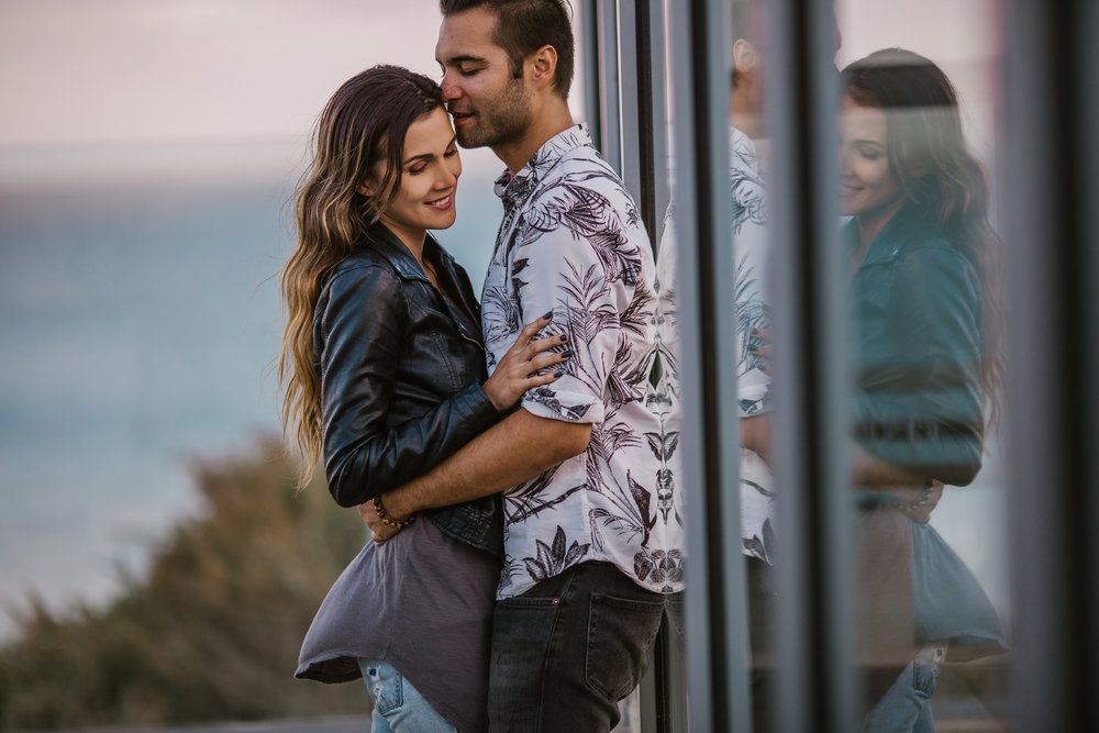san   diego wedding photographer | woman in leather jacket holding man against   glass window