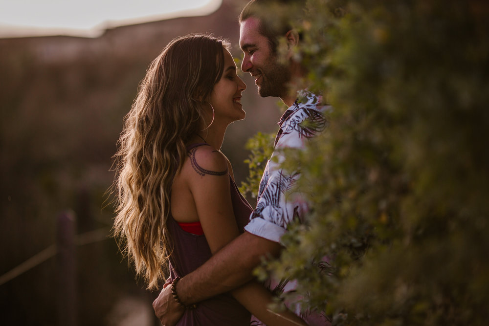 san   diego wedding photographer | man slightly covered by plants holding woman   from the front