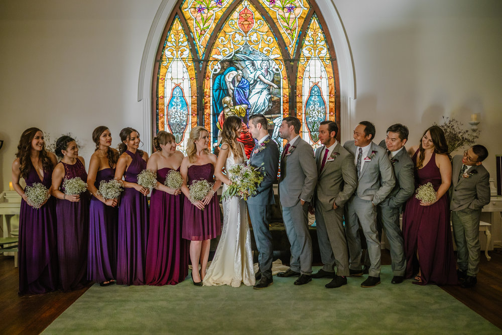 san diego wedding   photographer | bridesmaids and groomsmen lined up in front of stained glass
