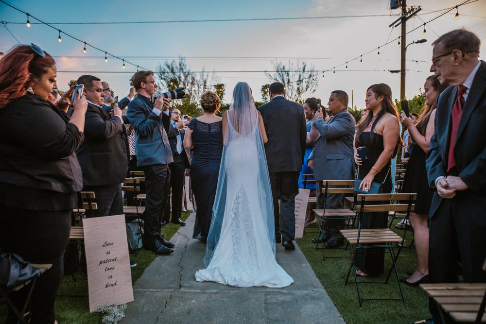 san diego wedding   photographer | bride being accompanied down the aisle by people