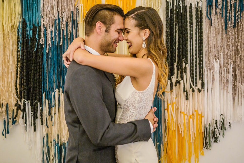 san diego wedding   photographer | couple hugging in front of wall decoration