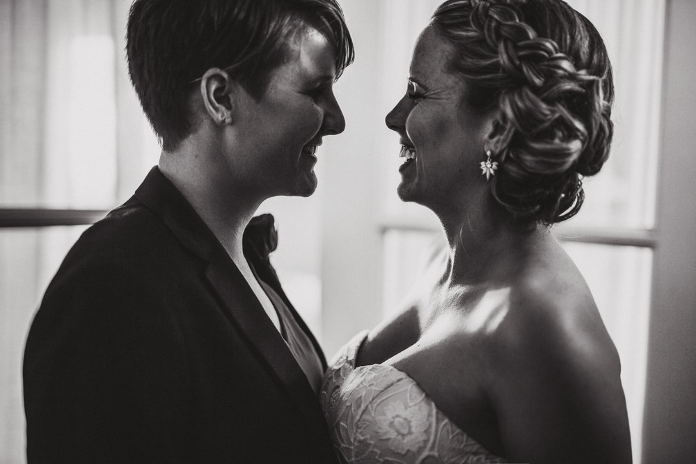 san diego wedding   photographer | woman in wedding dress and other woman in blazer smiling at   each other