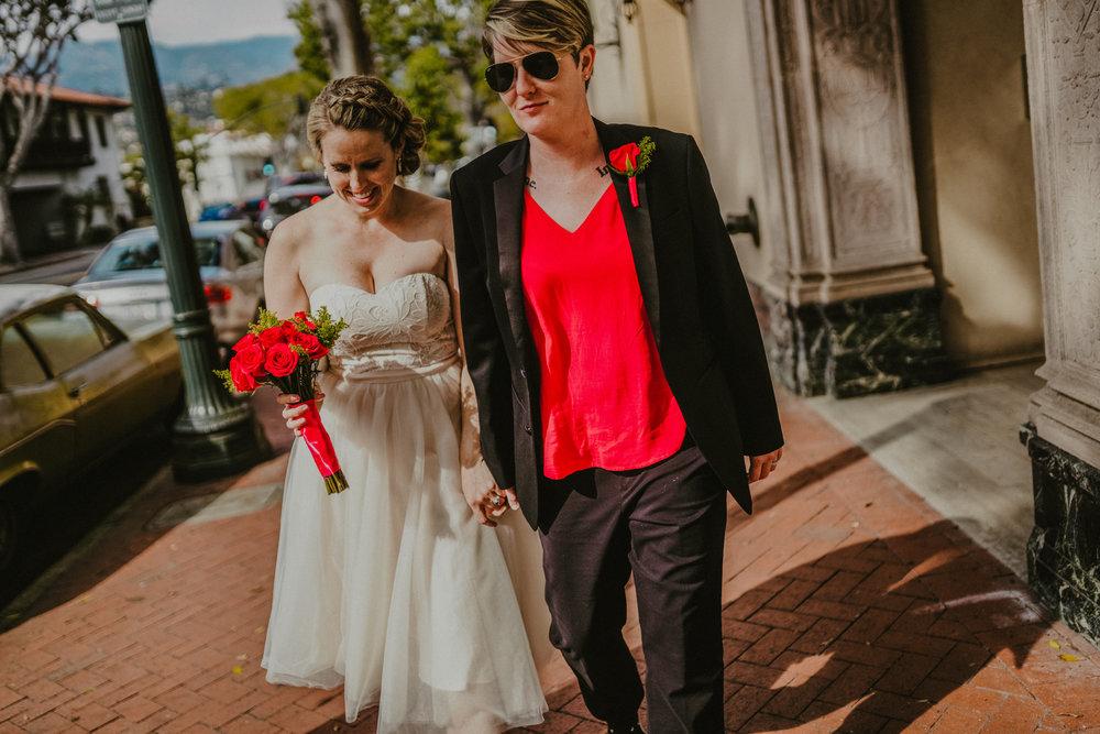 san diego wedding   photographer | woman holding woman's hand walking down sidewalk with bouquet