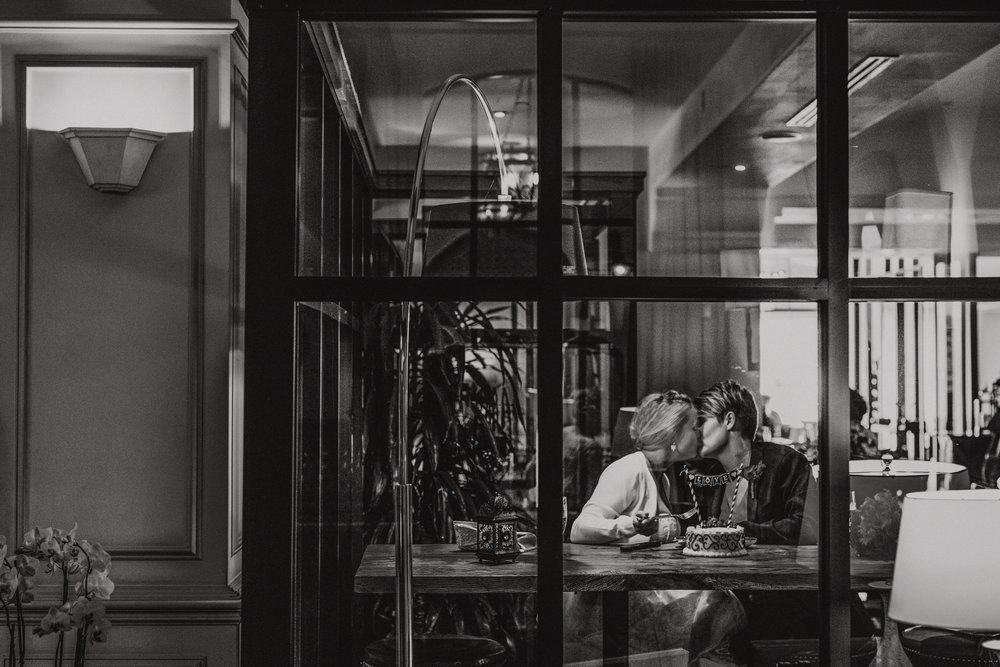 san diego wedding   photographer | monotone shot of women kissing seen through window panel