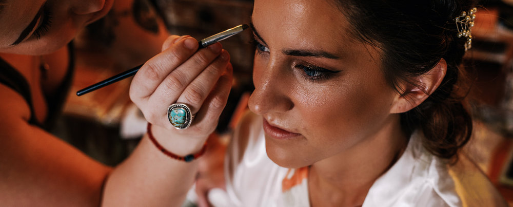 san diego wedding   photographer | woman with her eyes open being applied makeup on