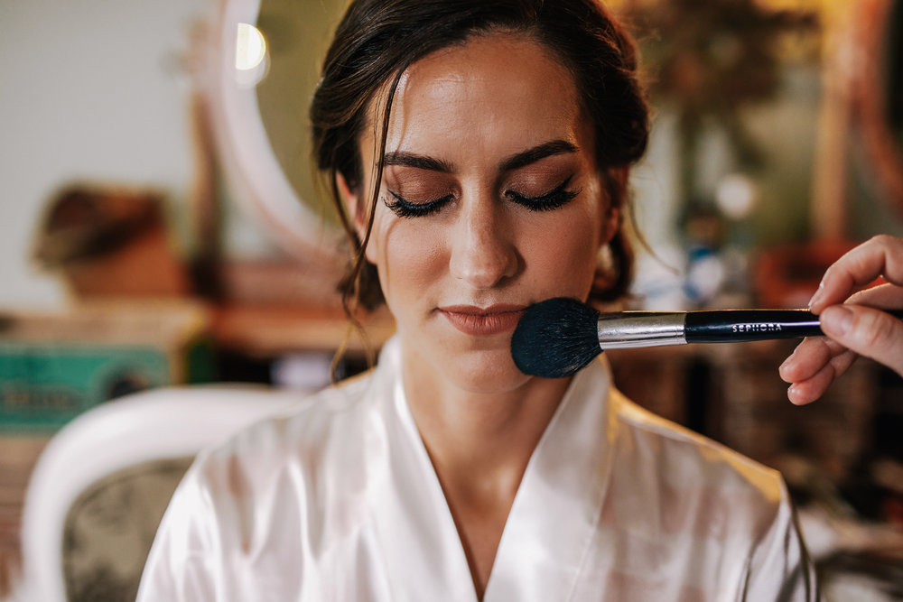 san diego wedding   photographer | woman with eyes closed being applied makeup on
