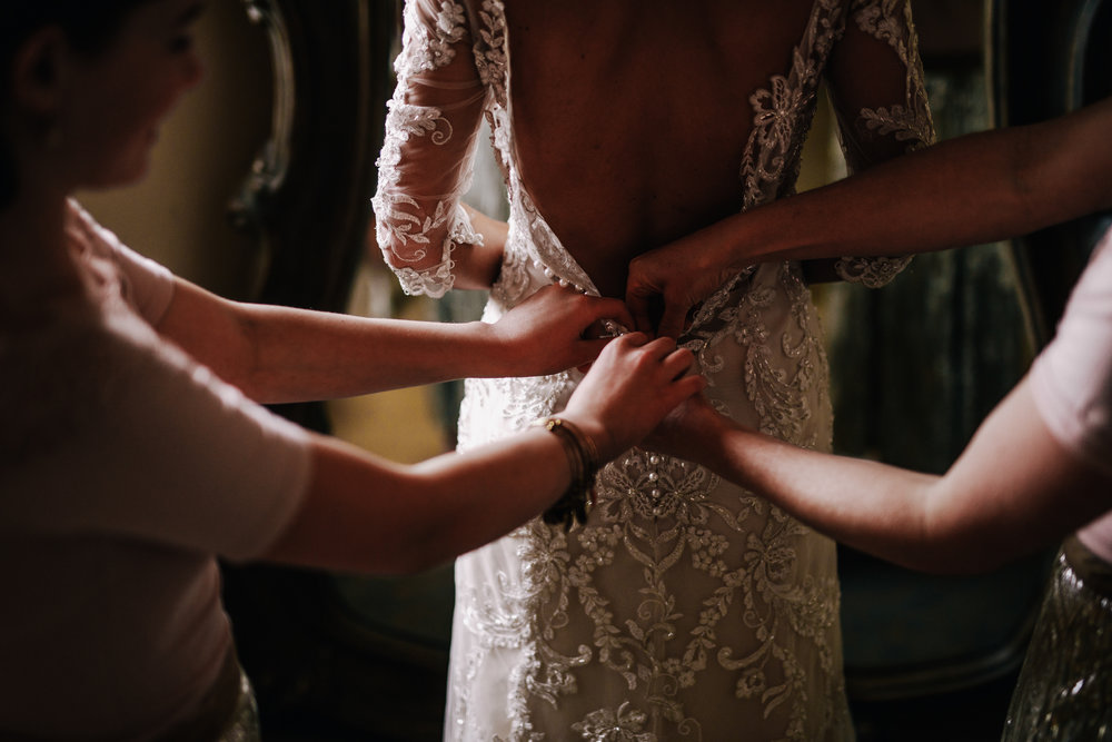 san diego wedding   photographer | woman's back while hands are trying to zip up her wedding   dress