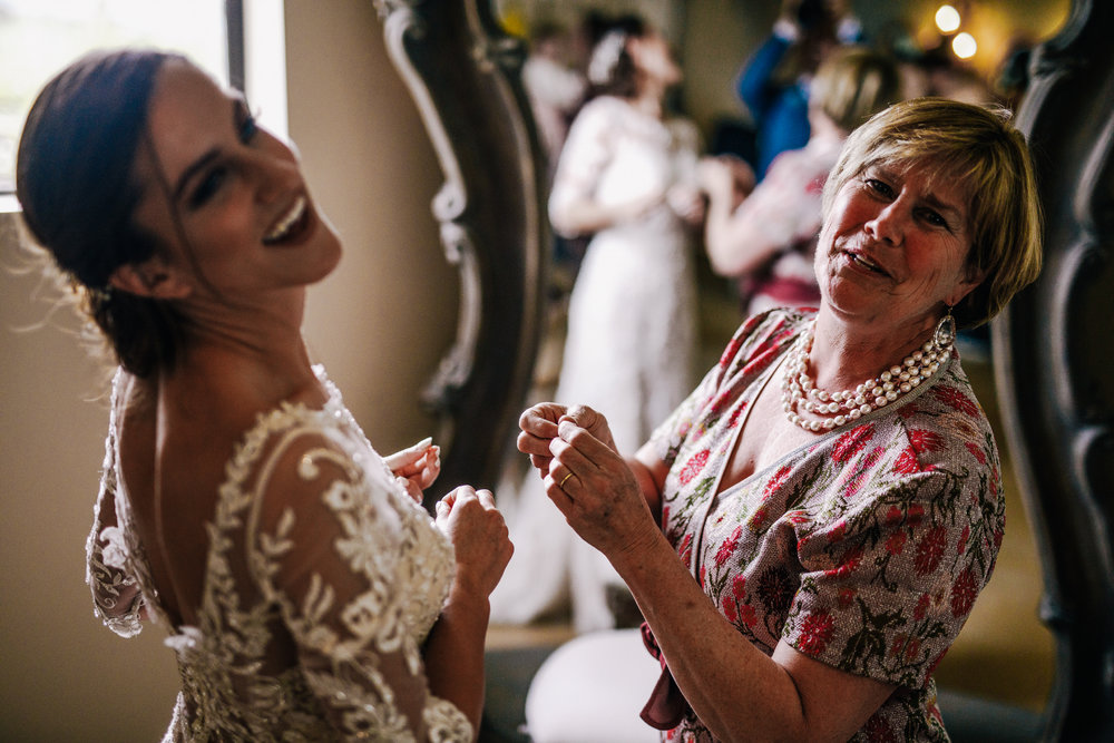san diego wedding   photographer | bride laughing with woman in red floral dress looking back