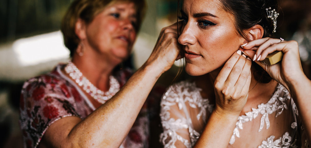 san diego wedding   photographer | bride putting on her earrings while woman in red floral dress   helps her looking at a mirror