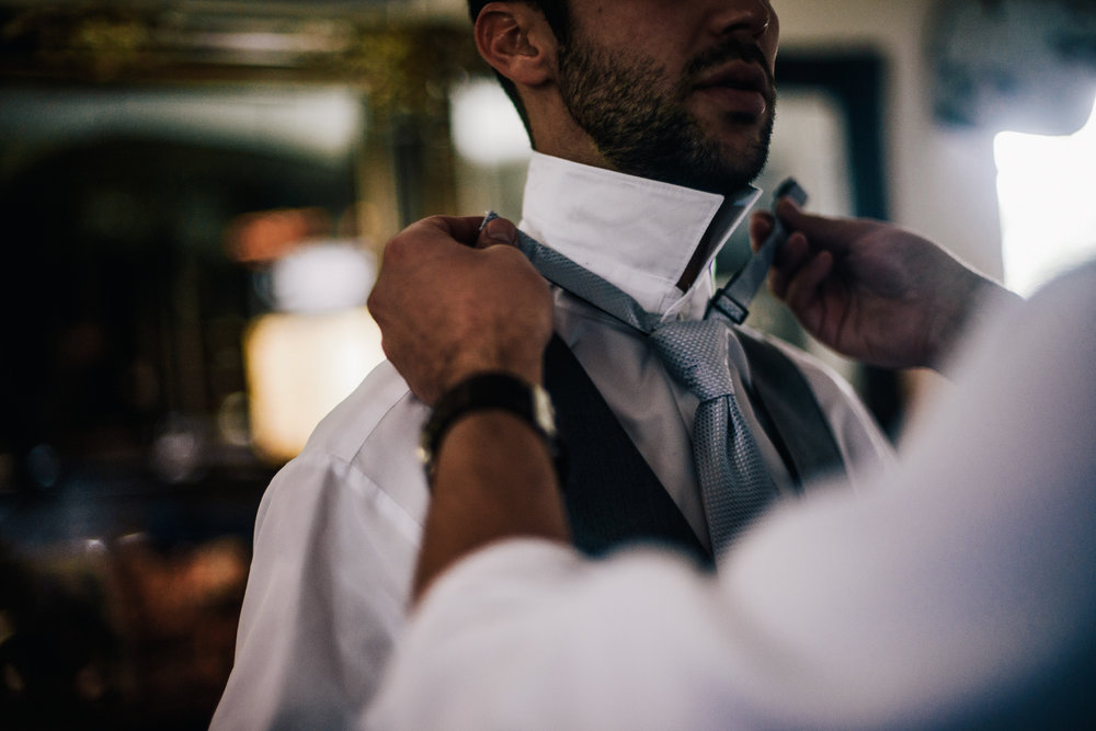 san diego wedding   photographer | man wearing vest being helped out with his tie