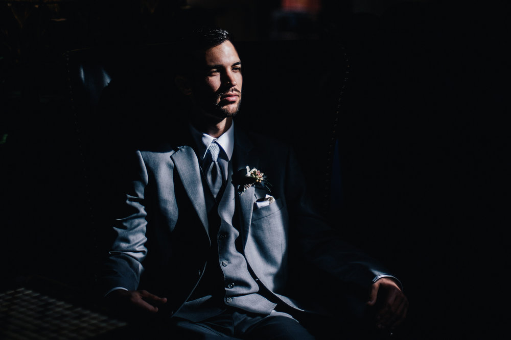 san diego wedding   photographer | man in grey suit sitting down being illuminated by ray of   sunlight