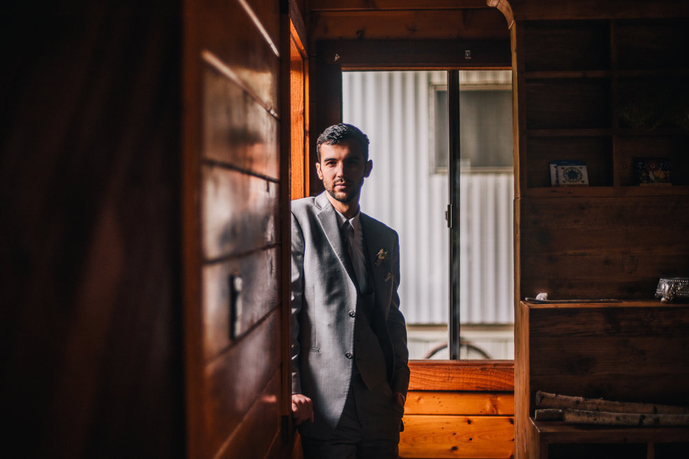san diego wedding   photographer | man in grey suit standing by windowsill in the sunlight