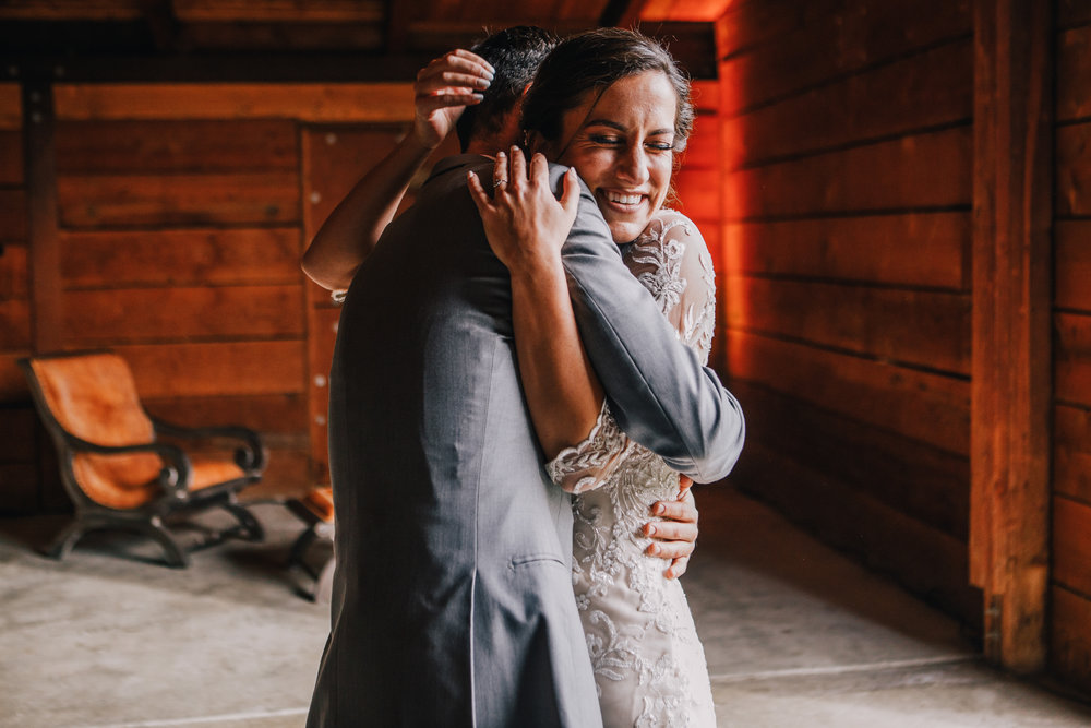 san diego wedding   photographer | groom hugging bride from her front inside barn