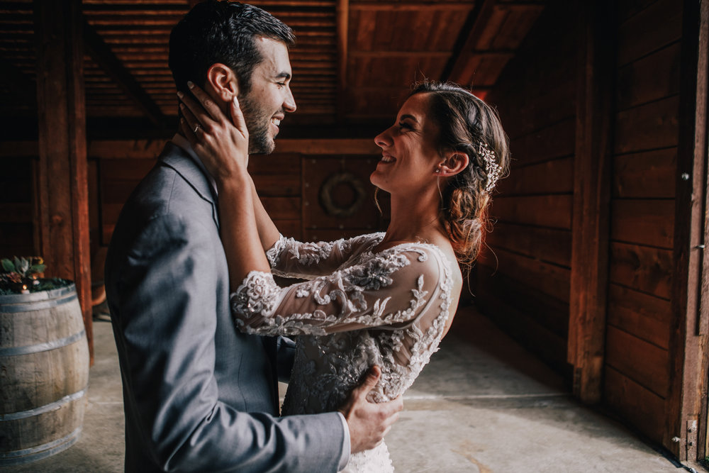 san diego wedding   photographer | married couple with bride holding groom's face and groom's   hands on bride's waist inside barn