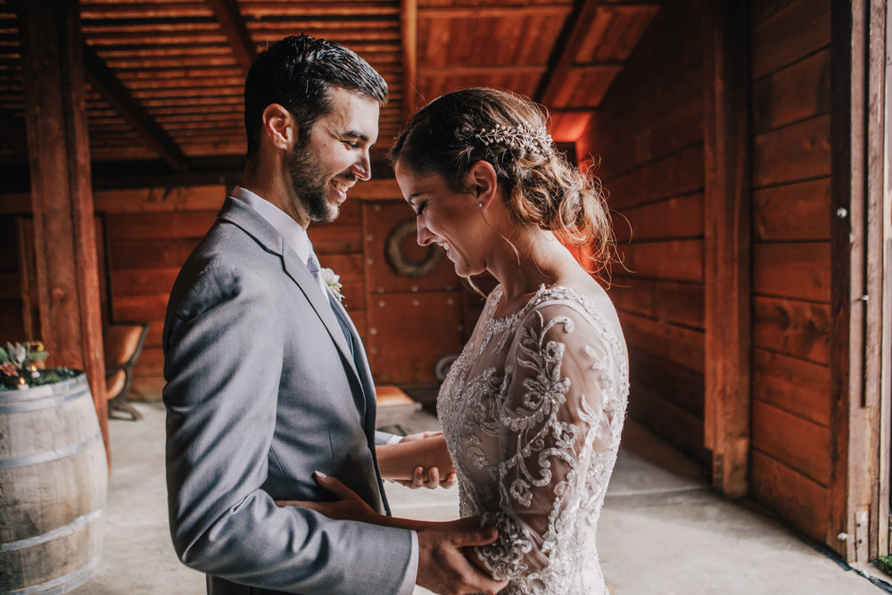 san diego wedding   photographer | groom holding bride's arms while smiling and looking down   inside barn