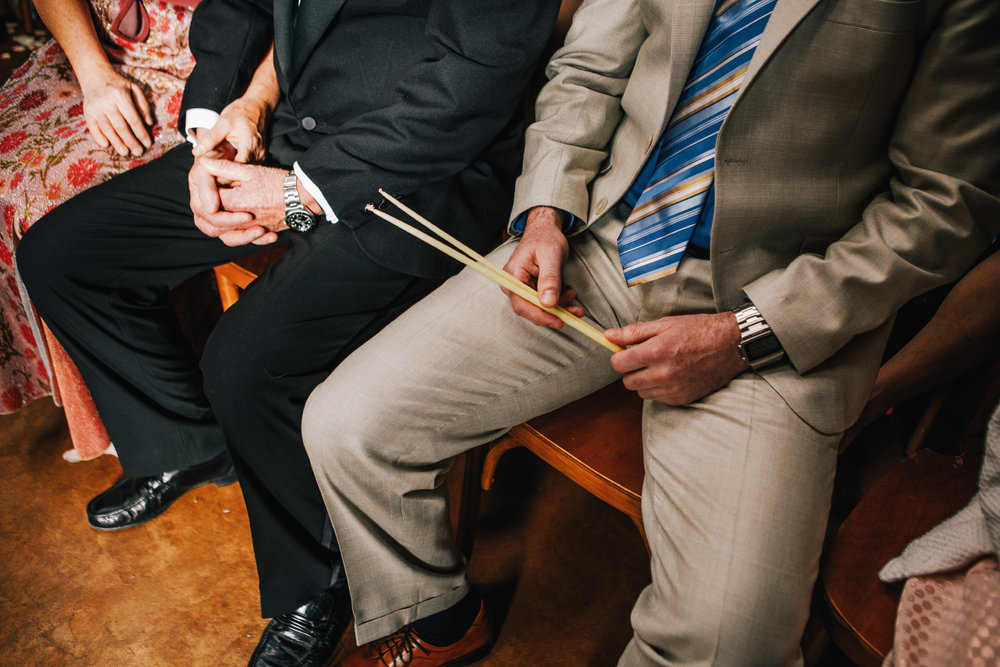 san diego wedding   photographer | lower body of people sitting in the crowd with a man holding   drumsticks