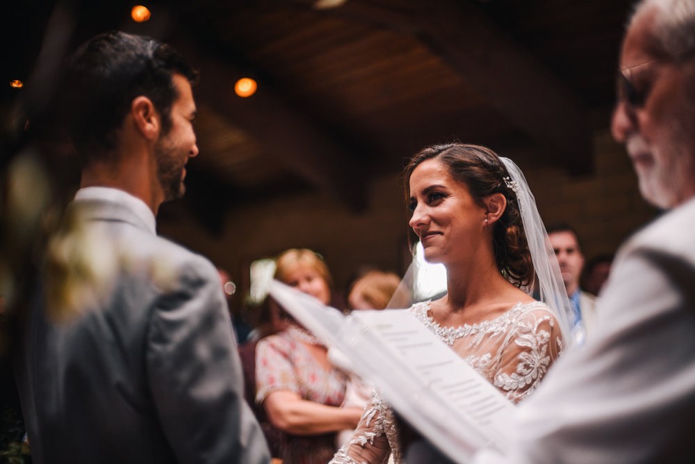 san diego wedding   photographer | bride and groom smiling at each other in front of wedding   officiator with a crowd behind them
