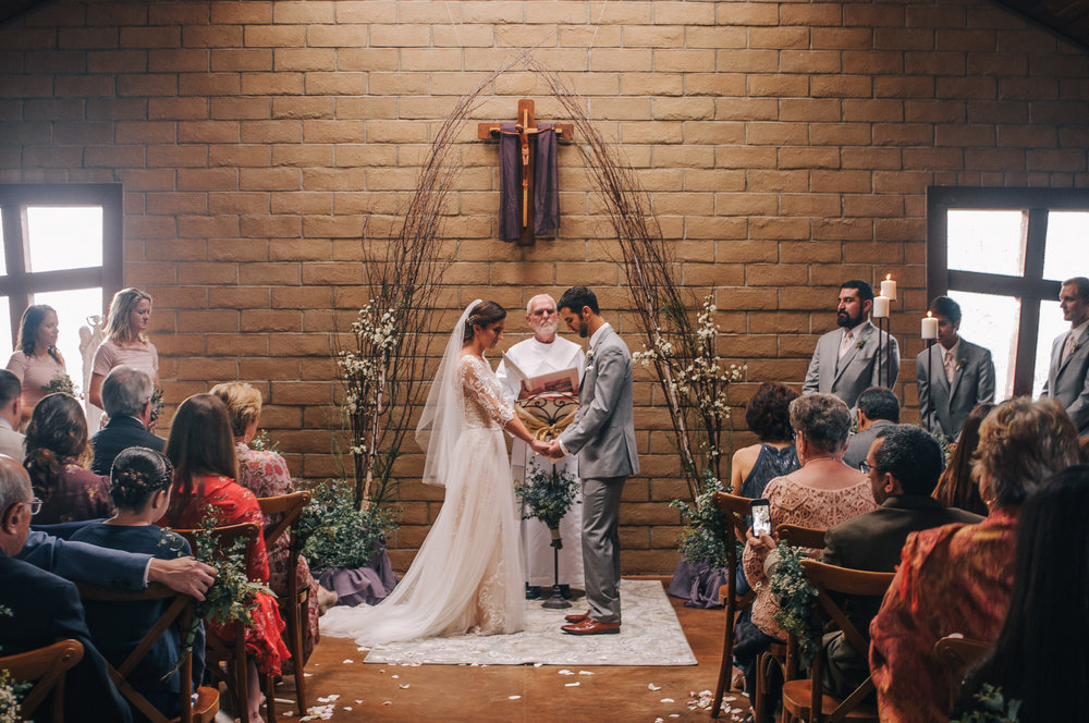 san diego wedding   photographer | bride and groom holding hands while looking down in front of   officiator with crowd watching