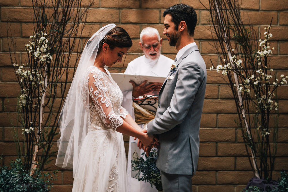 san diego wedding   photographer | bride and groom looking down holding hands with wedding   officiator reading something behind