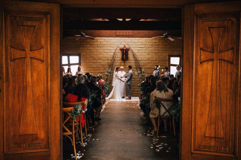 san diego wedding   photographer | bride and groom holding hands down the aisle seen through   chapel door