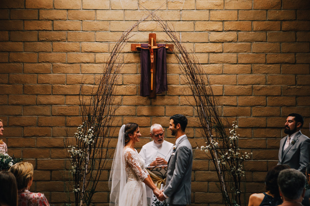 san diego wedding   photographer | bride and groom holding hands looking at each other down the   aisle under crucifix