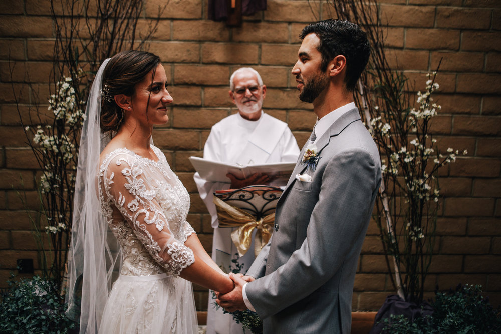 san diego wedding   photographer | bride and groom holding hands looking at each other smiling in   front of smiling officiator