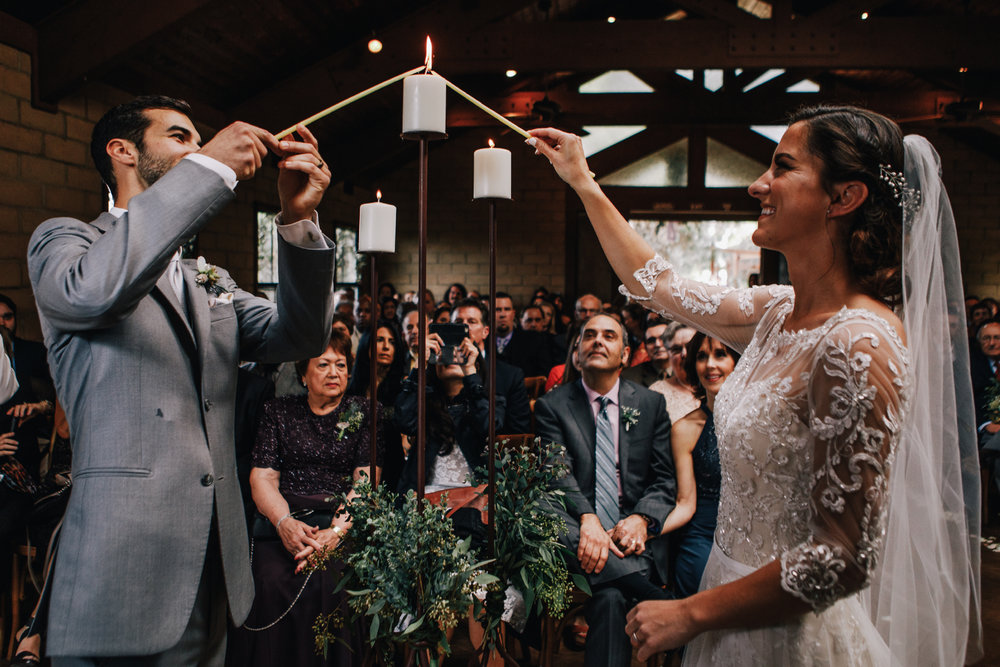 san diego wedding   photographer | bride and groom smiling while lighting candles from a thick   candle